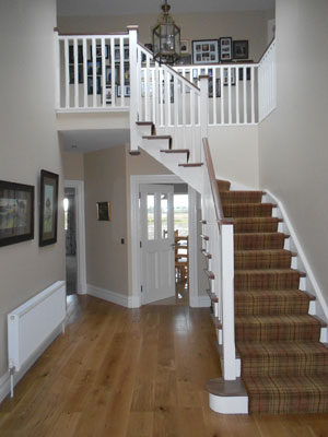 THe large inviting hallway also includes a finely detalied dog stairs with a carpet runner covering the steps and risers.