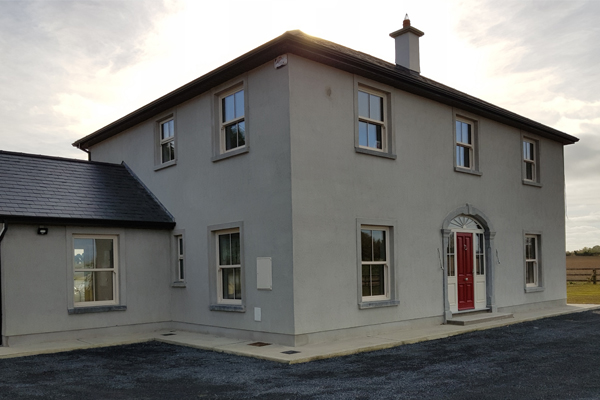 Traditionally styled dormer bungalow front with a range of one-off architectural features built in concrete block and rendered constructed in 2016 in Kilkenny, Ireland.